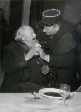 """PHOTO ORIGINALE / THEME """"1954, L'Abbé Pierre lance la Providence des sans logis, ici un policier s'occupant d'un sans abri"""""""