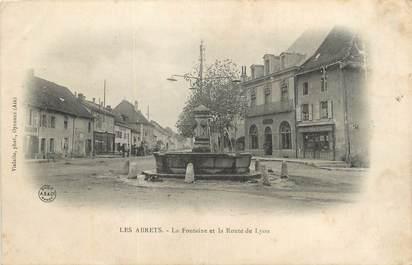 """CPA FRANCE 38 """"Les Abrets, La fontaine et la route de Lyon""""."""