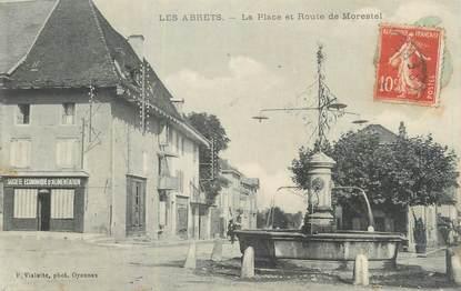 """CPA FRANCE 38 """"Les Abrets, La Place et route de Morestel""""."""