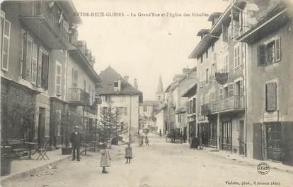 """CPA FRANCE 38 """"Entre Deux Guiers, la grande rue et l'église des Echelles"""""""